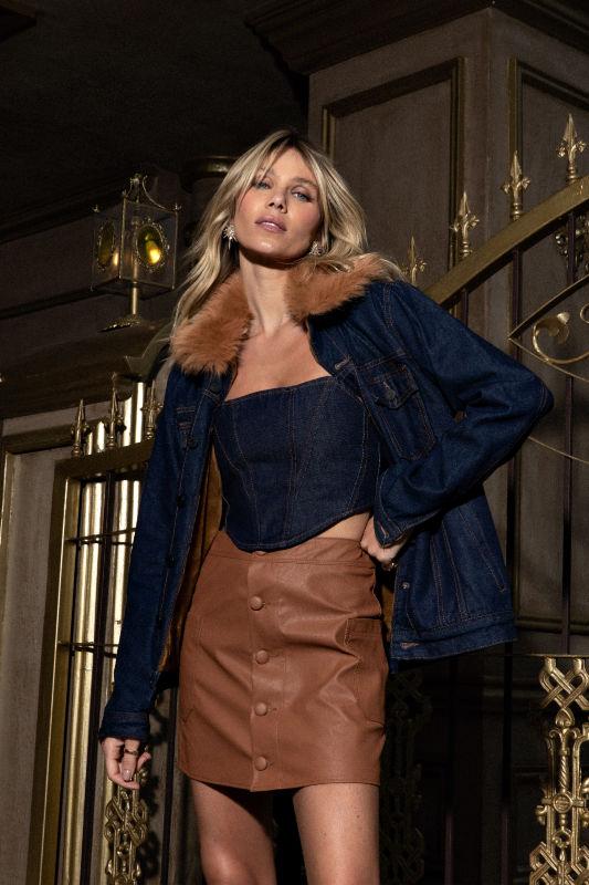 Modelo feminino de macacão jeans segurando-se ao parapeito de uma ponte de aço.